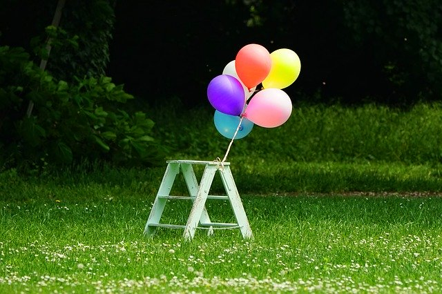 Balloons tied to a small step stool in a backyard
