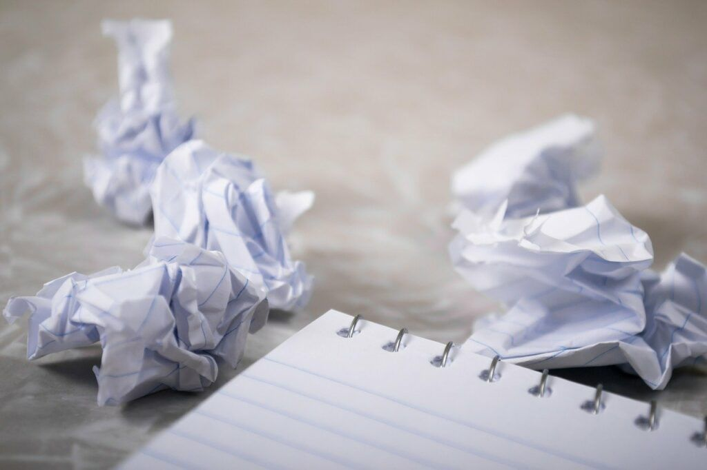 Crumpled paper next to notepad