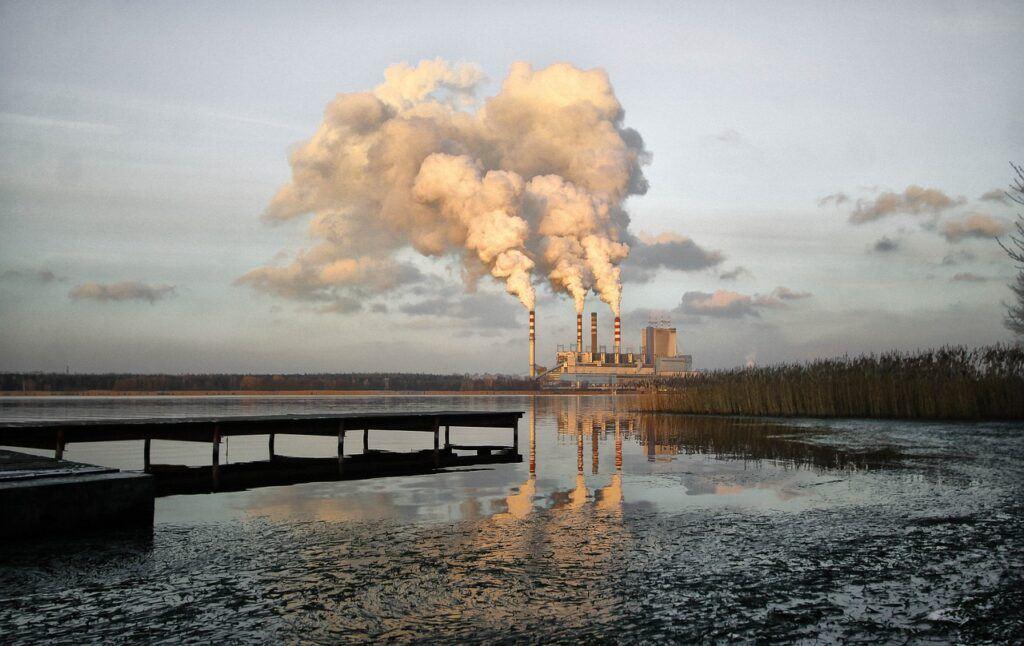 Factory pumping smoke next to lake