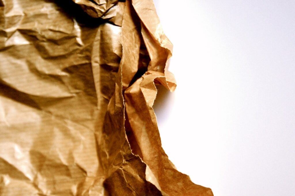 Crumpled recycled paper on white backdrop