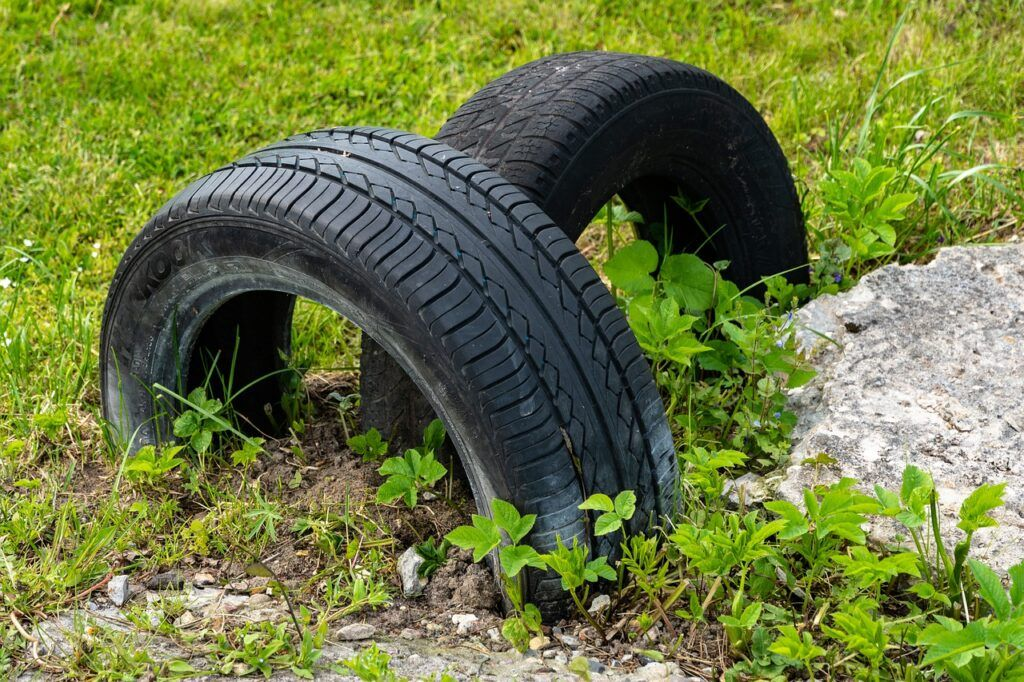 Car tires in dirt and plants