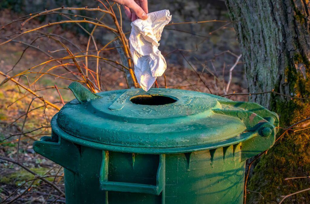 Hand placing used trash in green bin