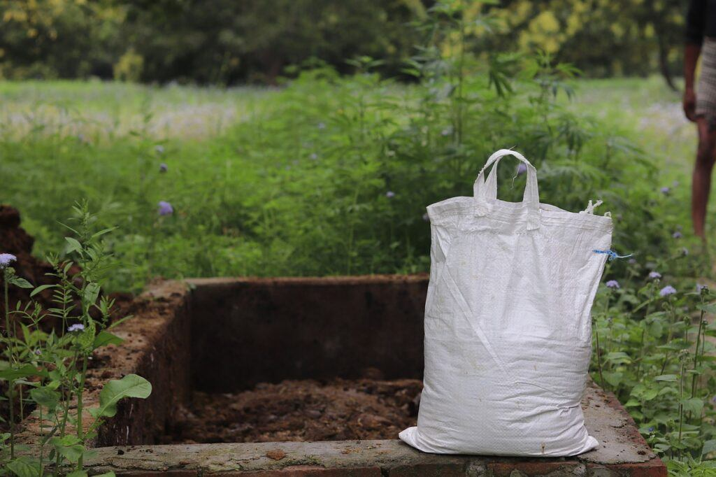 White bag next to compost pile