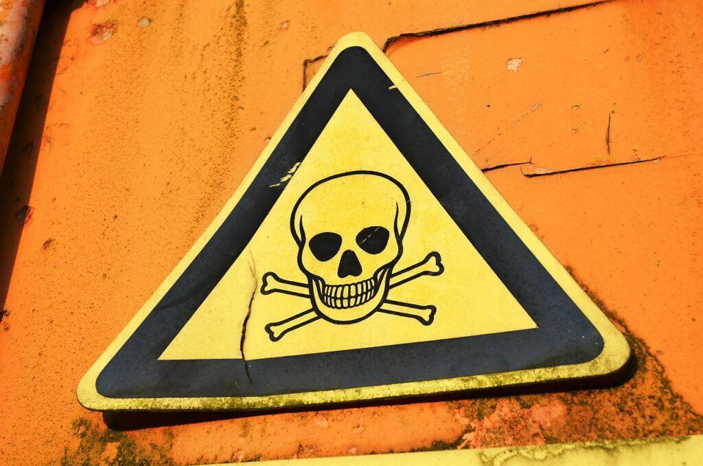 Warning sign on orange wall