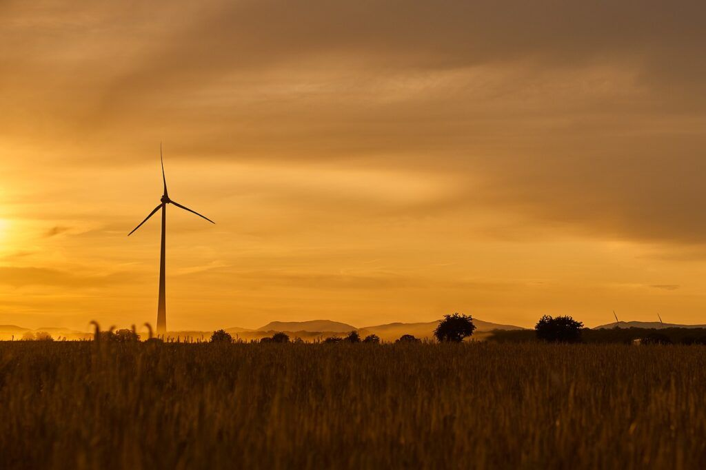 Windmill in field during sunset