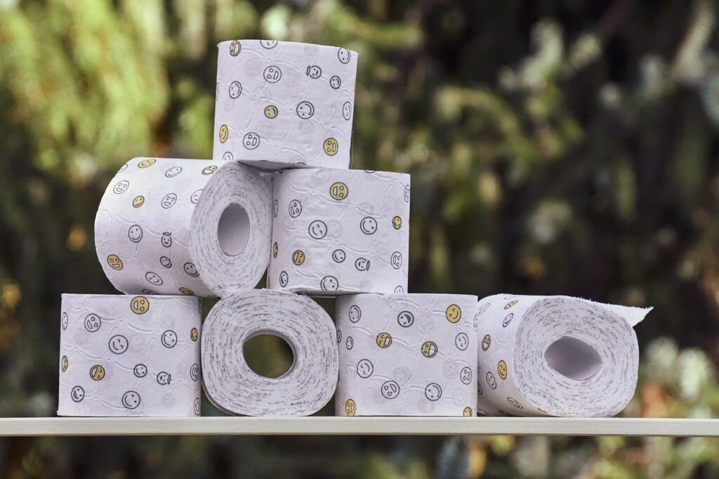 Rolls of toilet paper stacked on table with nature background.
