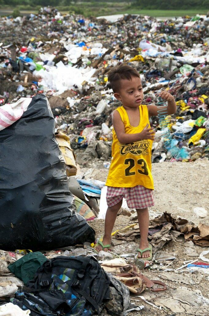 Kid playing with slinky in garbage dump
