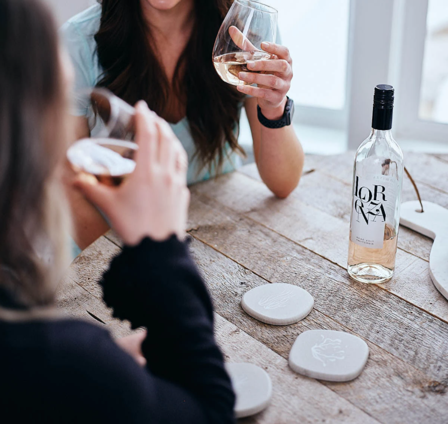 Women drinking out of glasses using Dorai River Rock Coasters