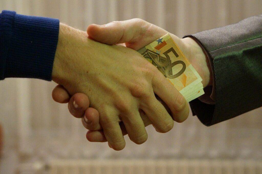 Two hands shaking with money between the hands